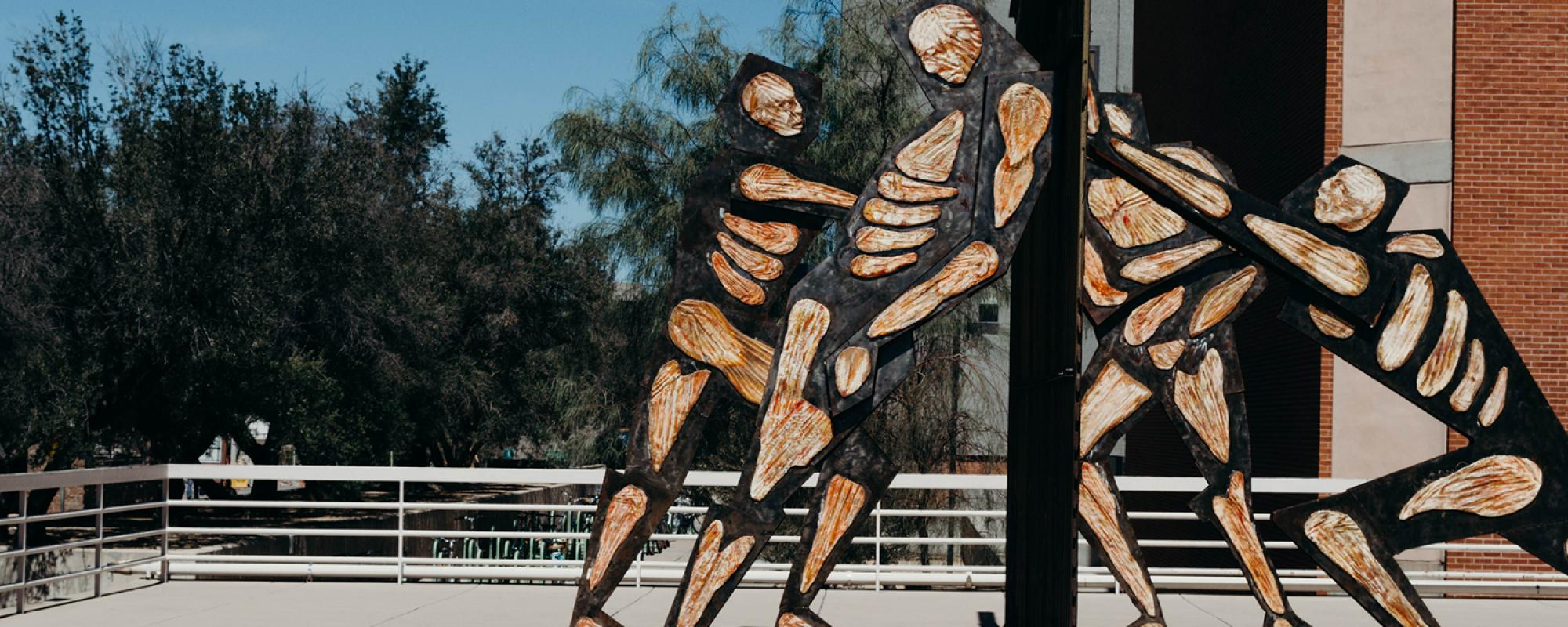 Statue showing muscle and bones human figures pushing on both sides of border wall